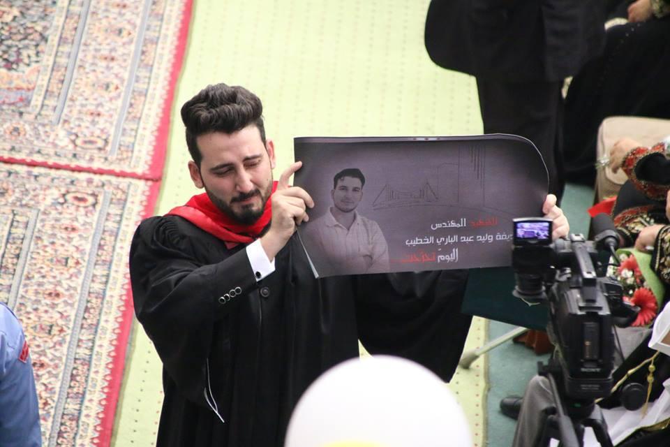 Abdullah Khateeb carrying his deceased brother's photo Huzaifa Al Khateeb (Facebook)