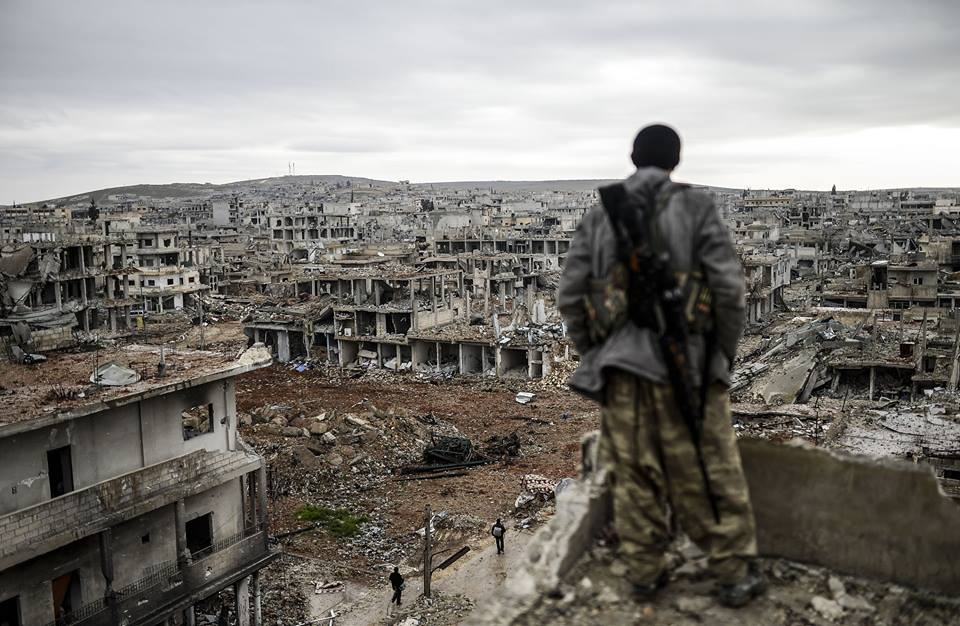 A Kurdish Syrian sniper on the roof of a destroyed building in the city of Ayn Arab, Kobani, June 2015 (France Press)