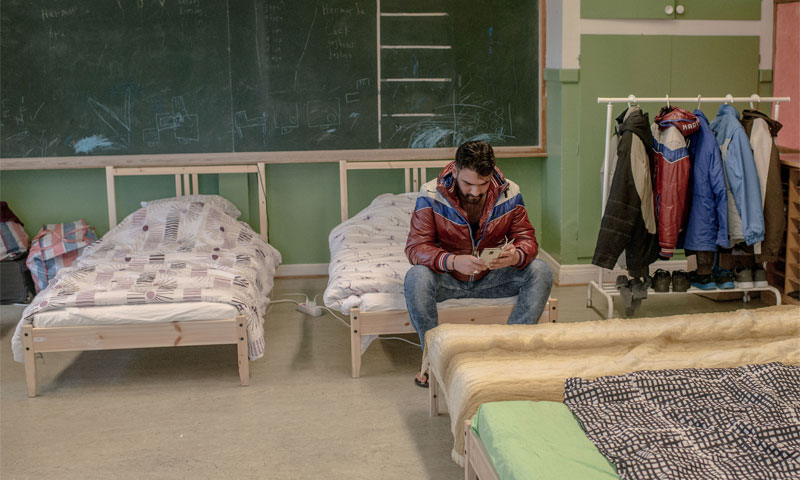 A Syrian refugee checking his phone in the asylum room in Sweden Camp, February 2016 (AFP)