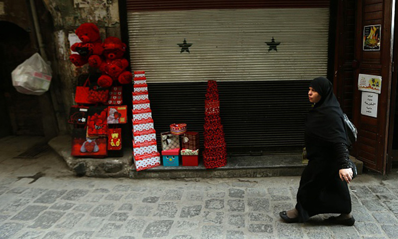 A Syrian woman walks next to a shop in Damascus, 10 February 2016 (AFP)