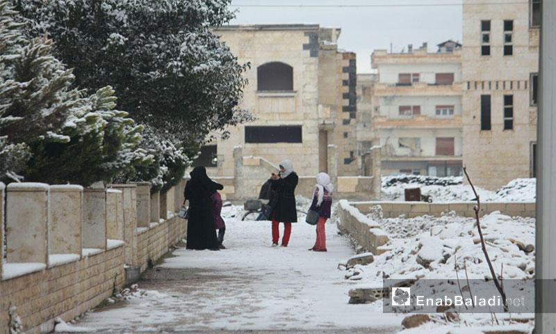 Women in the besieged al-Waer neighborhood during snowfall, 28 January 2017 (Enab Baladi)