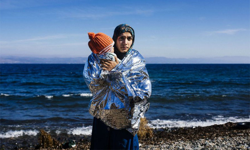 A Syrian refugee carrying her son as she arrives on Greek shores (EPA)