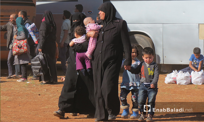 A mother and her children, who are originally from Homs, arriving to Idlib from Al-Waer neighborhood - 25 April 2017 (Enab Baladi)