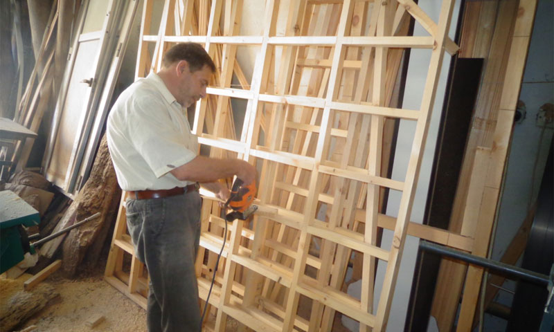 A displaced man from Rif-Dimashq is working in carpentry in Al-Suwayda