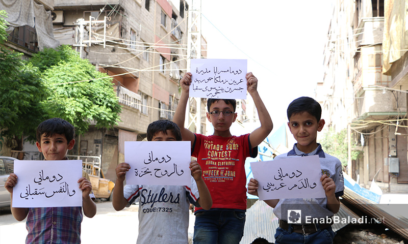 Children from Duma holding signboards that express the unity among cities and towns in Ghouta – April 11, 2017 (Enab Baladi)