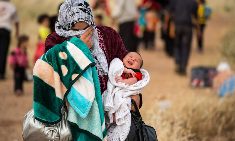 A Syrian refugee carrying her baby in the Zaatari refugee camp in Jordan - United Nations