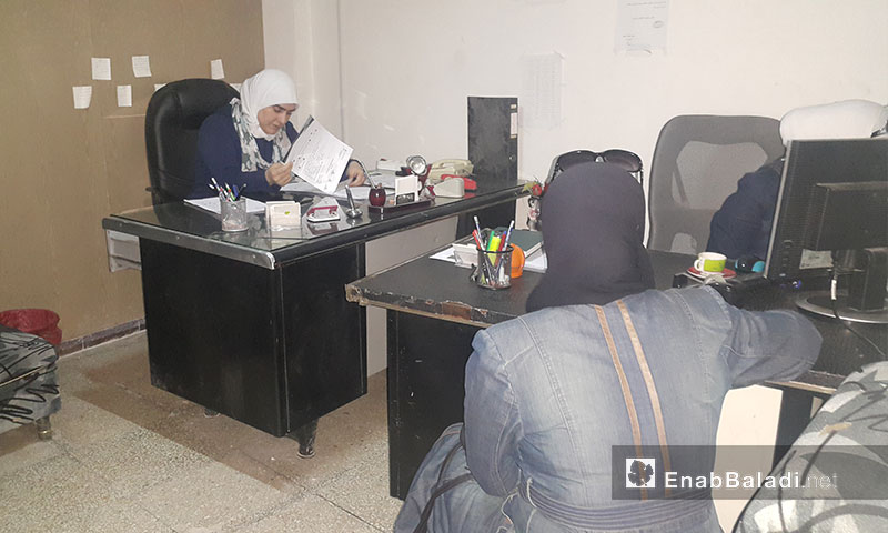 The head of the Women's Bureau of the Duma local council, Bayan Rayhan, receives women registered in the Karama project for grants, May 21, 2017 (Enab Baladi)