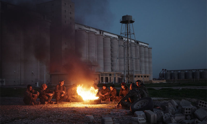 Kurdish fighters light a fire after taking control of Tell Hamis in al-Hasakah, February 2015 (The Independent)