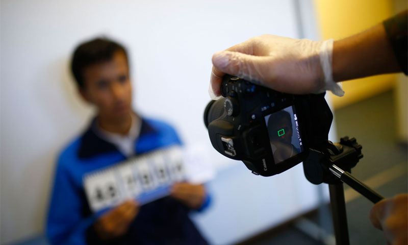 Taking a picture of a refugee in an immigrants camp, Germany (Reuters)