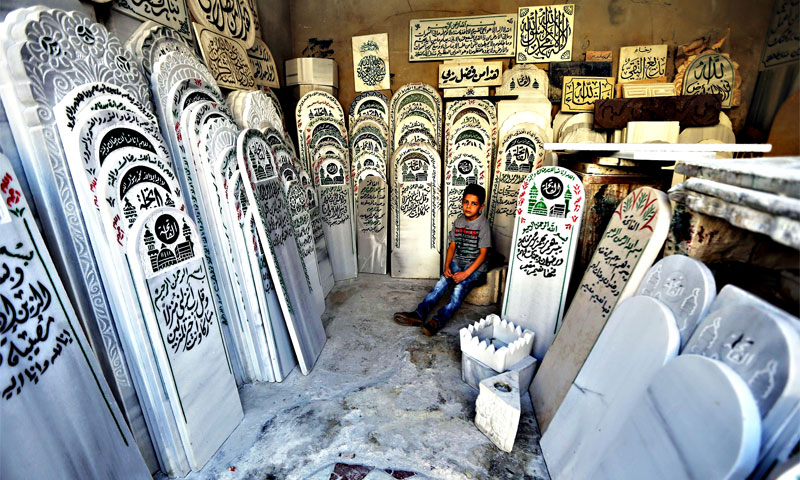 A sitting child surrounded by gravestones in a cemetery in Damascus - 29 September 2015