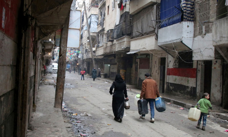 Citizens in Aleppo carrying containers to fill them with water (AP)