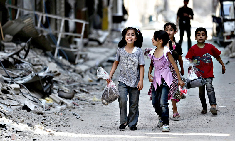 Children carrying bags of Eid al-Fitr clothes in Jobar district, Damascus - 2016 (Reuters)