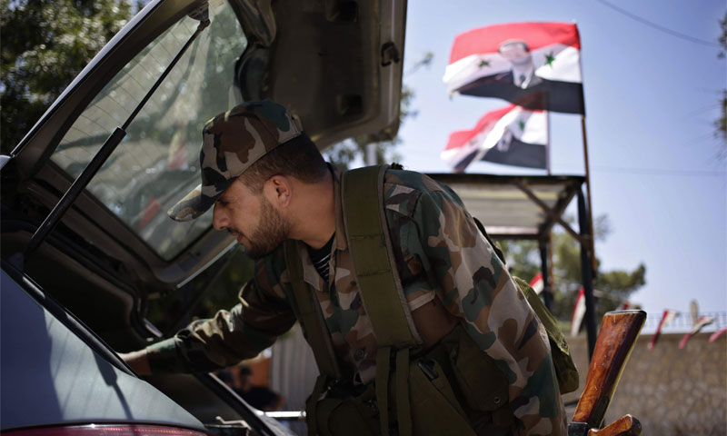 An officer at a checkpoint in Baghdad Street, Damascus - 21 August 2013 (AP)