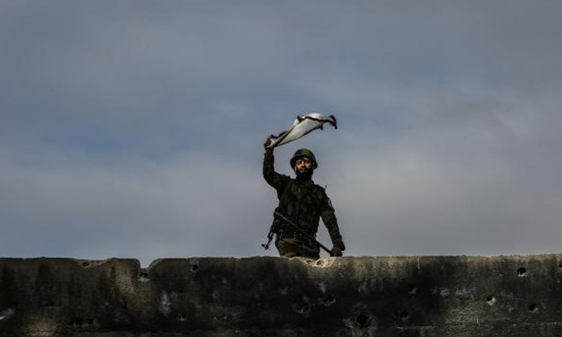 A cadet in the Jaish al-Islam Military Academy waves the academy's flag during a drill in January. The opposition group supervises a prison in the eastern suburbs of Damascus that is notorious for its abuse and torture methods. Photo by Mohammed Badra/EPA