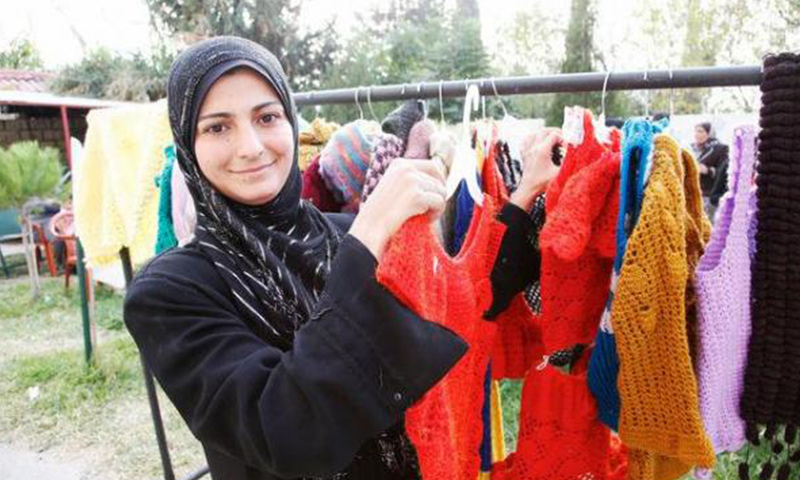 A woman from Homs, Syria, now a refugee in Lebanon, shows off knitted woolen clothes that she's learned how to make with support from the International Rescue Committee and UK aid. Photo by Russell Watkins/DFID