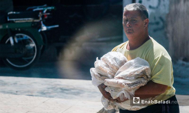 Citizen buying bread in al-Atarib, western Aleppo countryside, 4 August, 2017 (Enab Baladi)