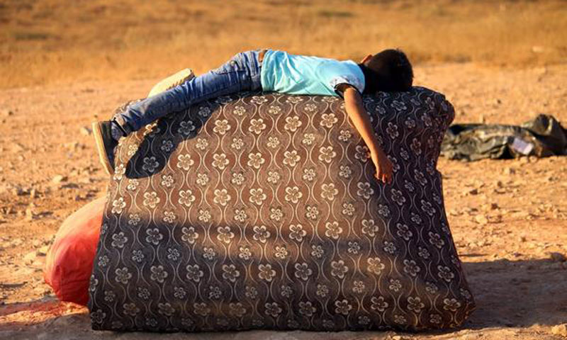 A child getting some rest while returning to Syria from Jordan with his family - August 29, 2017 (AFP)