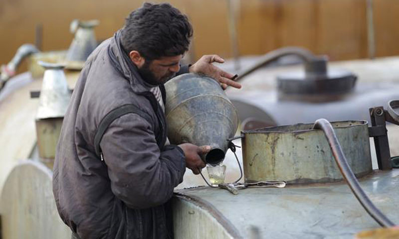 A worker inspecting the final oil product in rural Idlib - December 2015 – (Reuters)