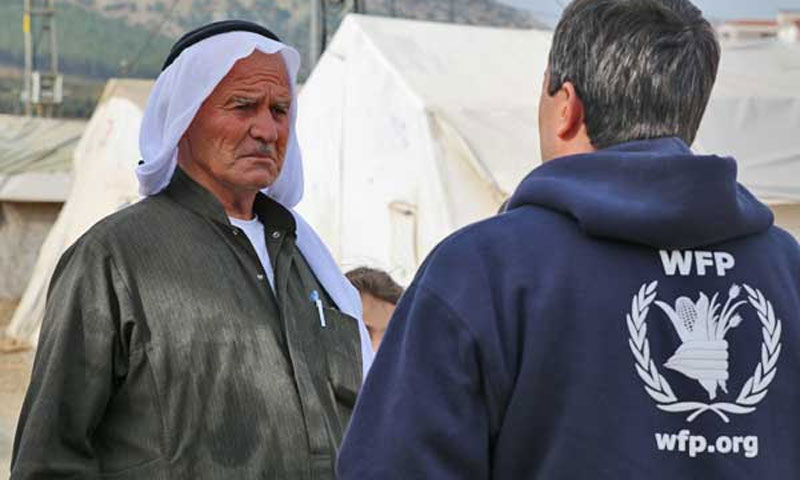 UNHCR employee in front of a Syrian elderly in a border refugee camp with Turkey (WPF)