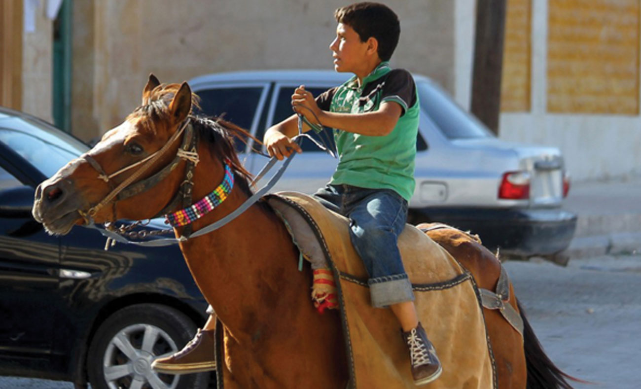 A Syrian child running away on a horse back in the city of Idlib after hearing the sound of an air raid - July 18, 2017 (AFP)