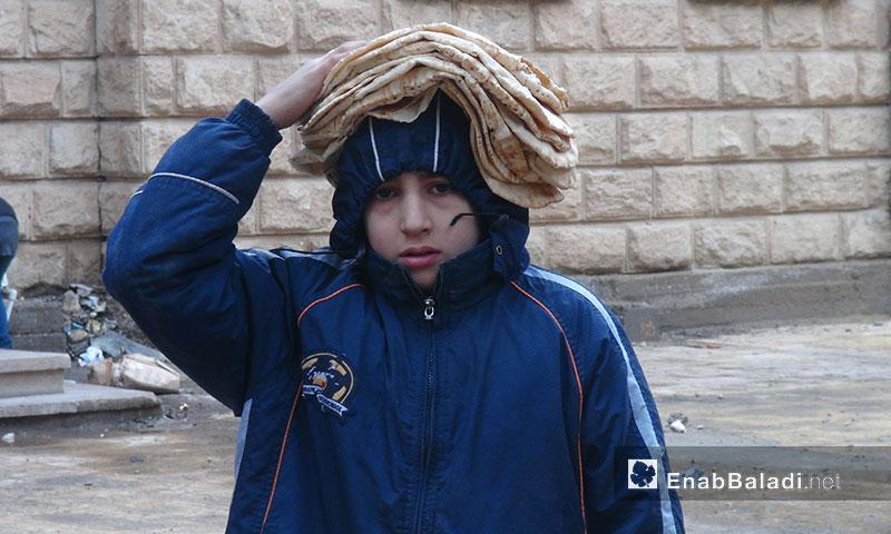 A child carrying bread over his head in al-Hamidiyeh neighborhood in Deir ez-Zor - 2013 (Enab Baladi)