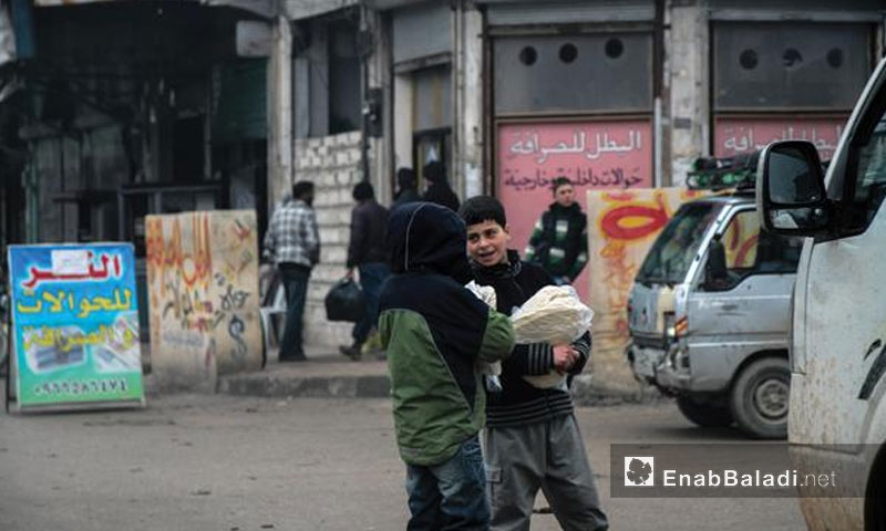 Children carrying bread in the morning in the city of Idlib - 17 January 2017 (Enab Baladi)