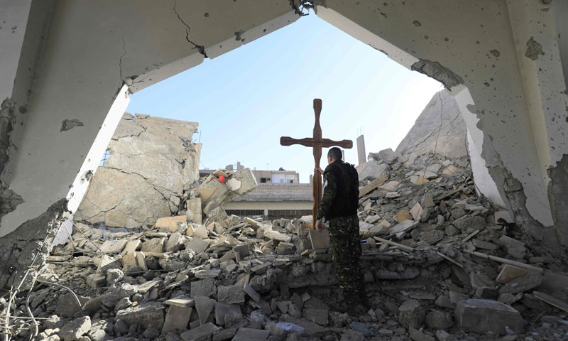 """A member of the """"Syrian Democratic Forces"""" placing a Cross over the rubble inside the ruins of the Armenian Catholic Martyrs' Church in the Syrian city of Raqqa - December 26, 2017 (AFP)"""
