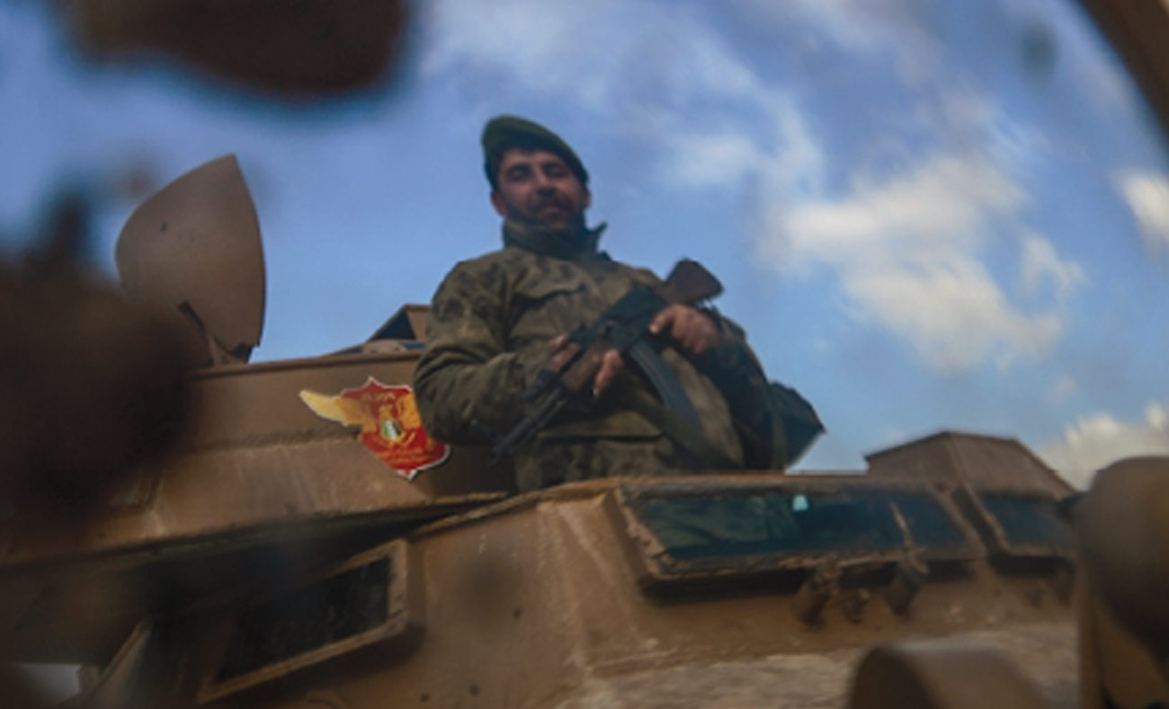 The reflection of the image of a fighter in the Syrian opposition backed by Turkey in the city of Azaz in northern Aleppo - 27 January 2018 (AFP)
