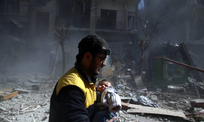 A member of the Civil Defence Organization in rural Damascus while rescuing an injured child in eastern Ghouta – (Reuters)