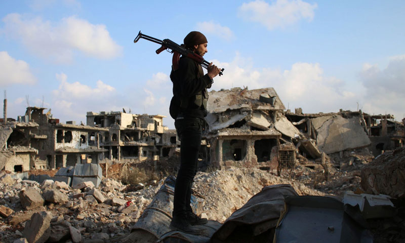 """A member of the """"Free Army"""" standing upon the rubble of the destroyed building in the city of Daraa (AFP)"""
