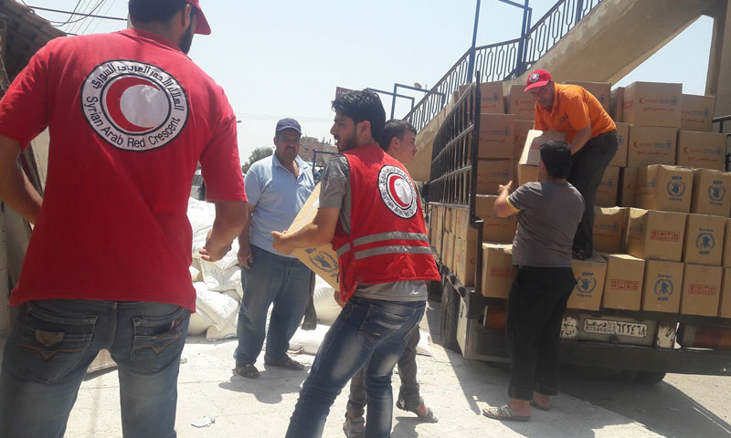 """The """"Syrian Red Crescent"""" teams distributing relief aids to the people in the city of al-Sanamayn in Daraa- September 2017 (Red Crescent)"""