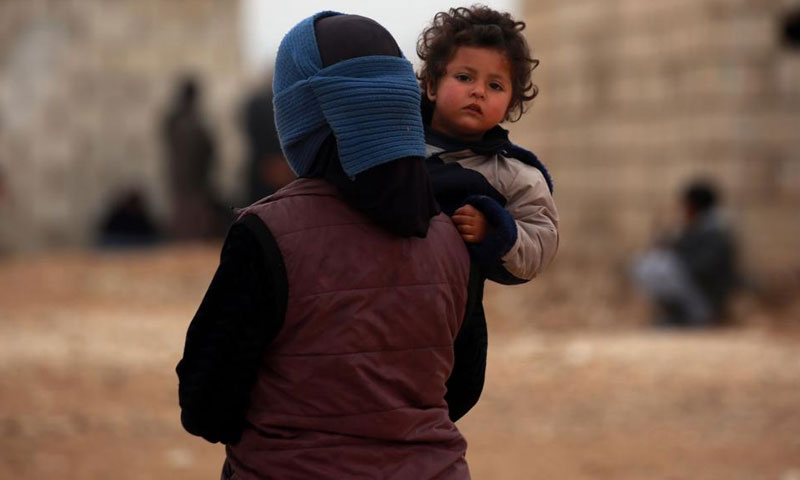 A Syrian woman displaced from Deir ez-Zor, carrying her child in a camp in Hasakah – February 26. 2018 (AFP)