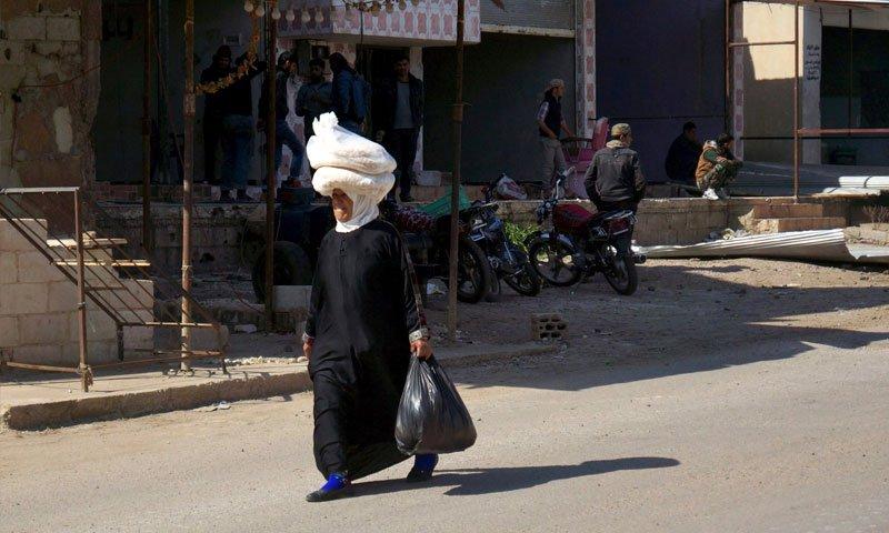 A women carrying bread over her head in the al-Ghariyah al-Gharbiyah town in rural Daraa – February 29. 2016 (Reuters)