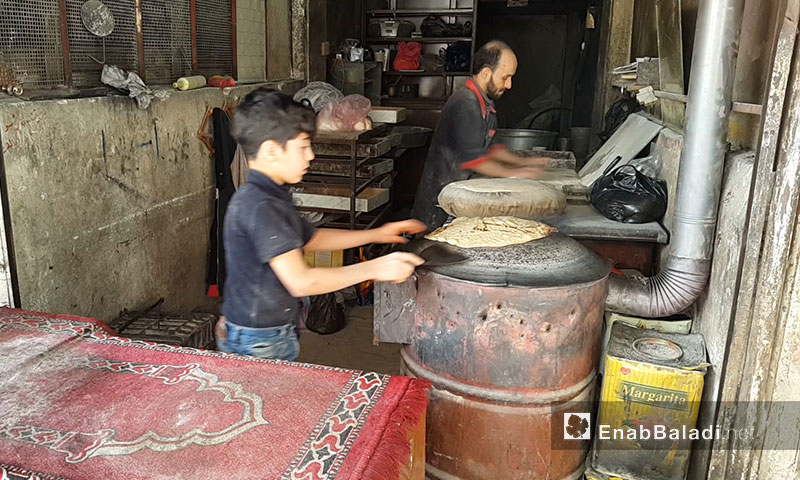 A child helping his father in baking bread in Eastern Ghouta – April 2017 (Enab Baladi)