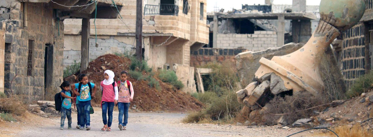 Children walking among the rubble of destroyed houses in the southern countryside of Daraa – September 17, 2018 (AFP)