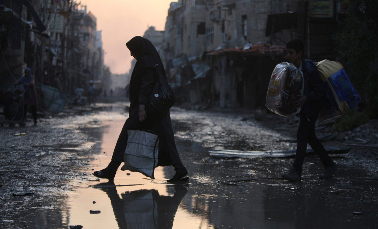 A woman crossing an abandoned road in the town of al-Hajirah in southern Damascus – (Reuters)