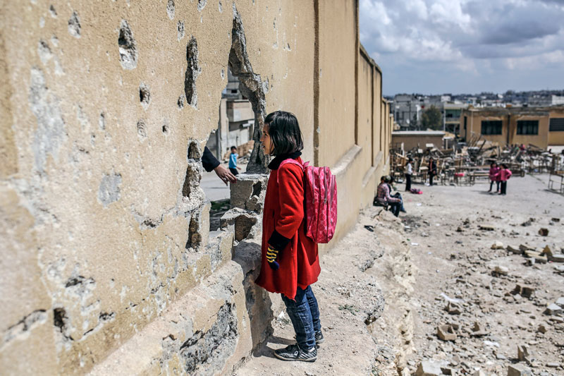 A girl standing in the school courtyard (AFP)