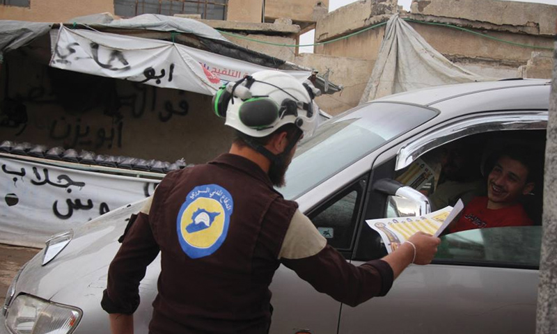 A Civil Defense member giving the campaign's brochures to drivers in Idlib – May 29, 2018 (Civil Defense's Twitter Account)