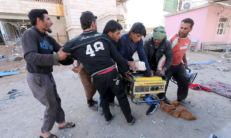 A group of people fighting over a looted electricity generators in Al-Shaddadi city, February 26, 2016 (Reuters)