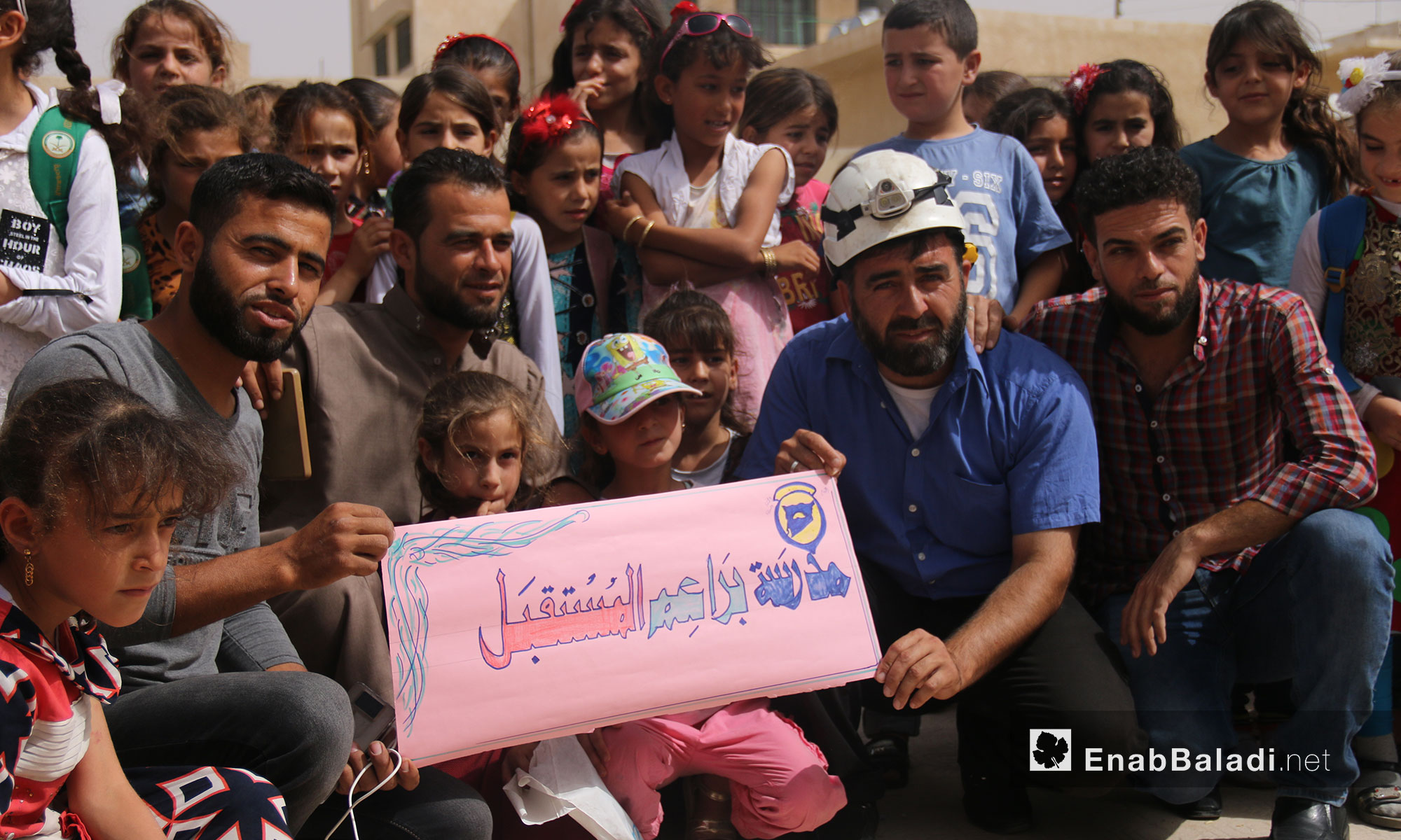 """Teachers and students from """"The Buds of the Future"""" school stand in solidarity with the """"White Helmets"""" in rural Idlib (the sign in the picture says: The Buds of the Future School) – July 25, 2018 (Enab Baladi)"""