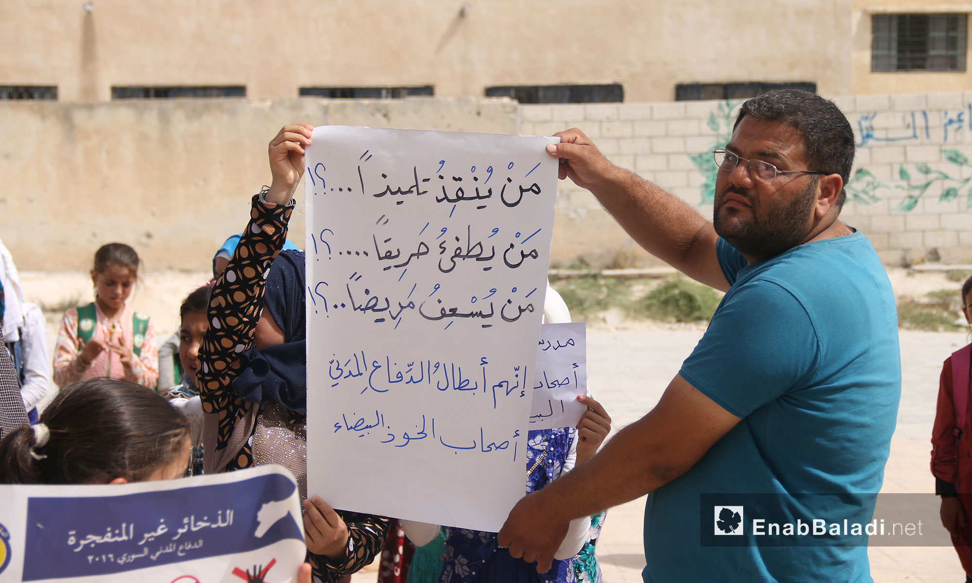 """Teachers and students from """"The Buds of the Future"""" school stand in solidarity with the """"White Helmets"""" in rural Idlib (the sign in the picture says: Who saves a student? Who puts a fire down? Who rescues patients? The White Helmets Do) – July 25, 2018 (Enab Baladi)"""