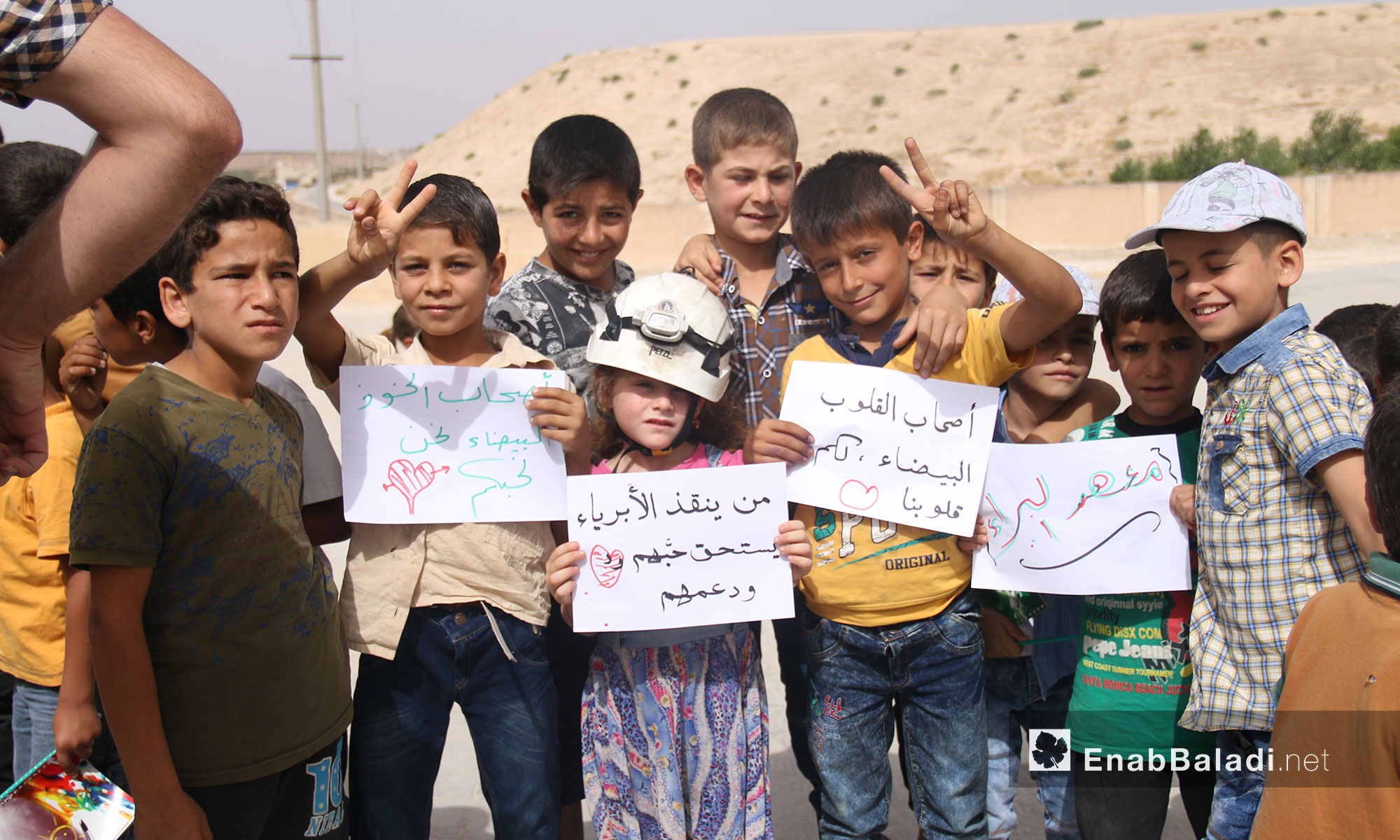 """Teachers and students from """"The Buds of the Future"""" school stand in solidarity with the """"White Helmets"""" in rural Idlib (the signs from left to right say:  The White Helmets, We Love You; That Who Saves Innocents Deserves their Love and Support; The White Helmets, You Have Our Hearts; """"al-Baraa Institute"""") – July 25, 2018 (Enab Baladi)"""