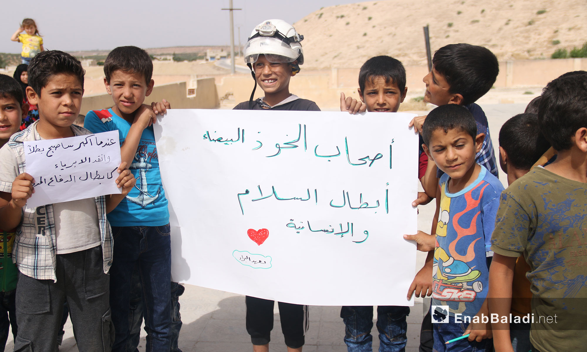 """Teachers and students from """"The Buds of the Future"""" school stand in solidarity with the """"White Helmets"""" in rural Idlib (The sign in the picture says:  The White Helmets are Heroes of Peace and Humanity) – July 25, 2018 (Enab Baladi)"""