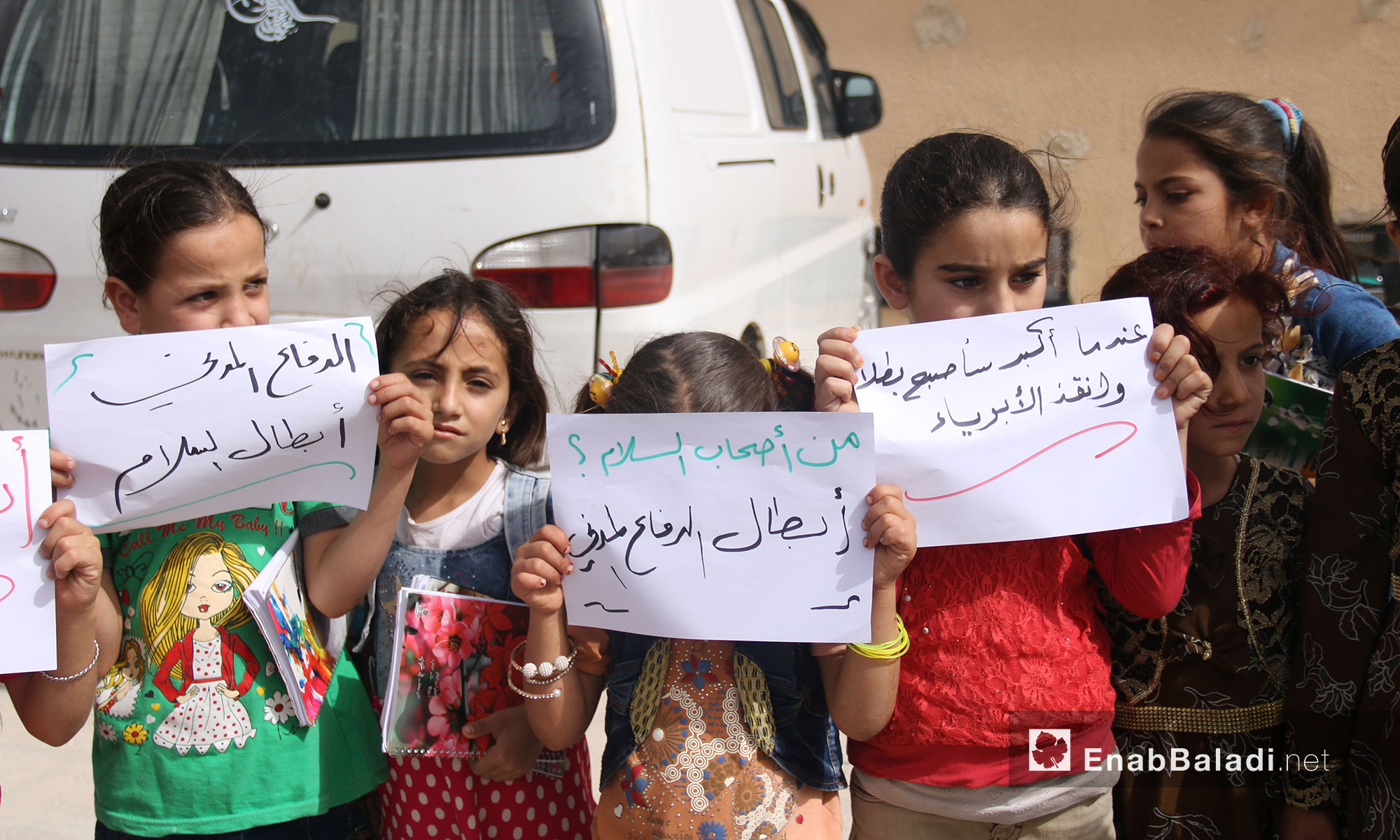 """Teachers and students from """"The Buds of the Future"""" school stand in solidarity with the """"White Helmets"""" in rural Idlib (The signs from left to right say:  Civil Defense are Peace Heroes, Who Are the Peace Keepers? The White Helmets; When I Grow up, I will be a Hero and Save the Innocent) – July 25, 2018 (Enab Baladi)"""