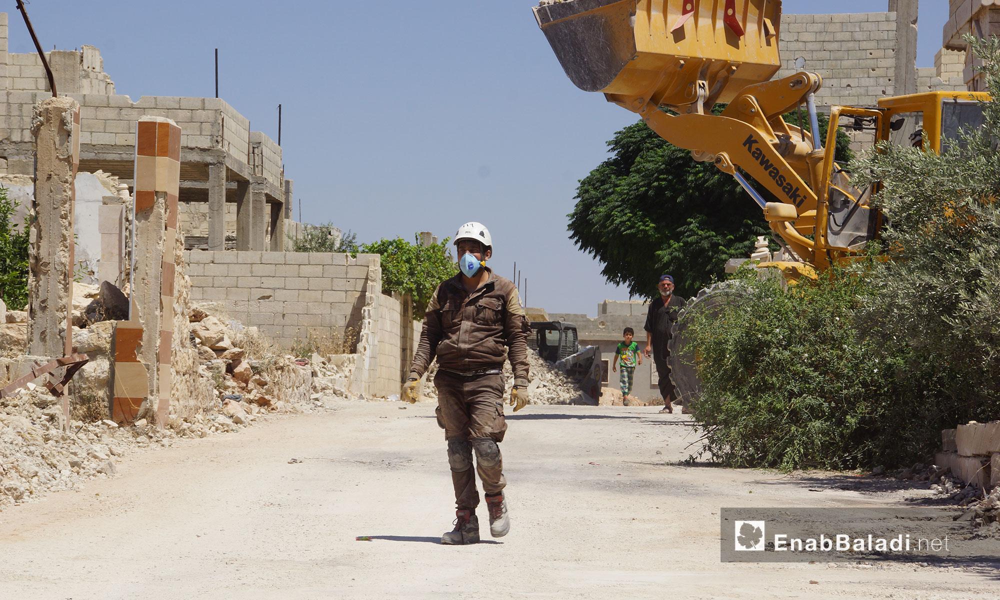 """Syrian Civil Defense"" members cleaning roads under the ""Earth Revival"" Campaign in the city of Murak, rural Hama - July 7, 2018 (Enab Baladi)"