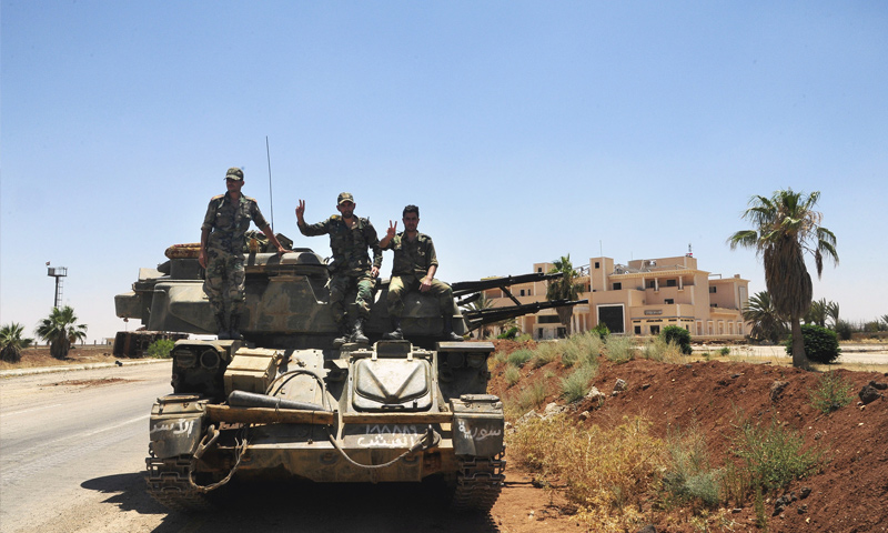Assad's forces troops raise their fingers in a sign of victory, after controlling al-Nassib border crossing – July 7, 2018 (AP)