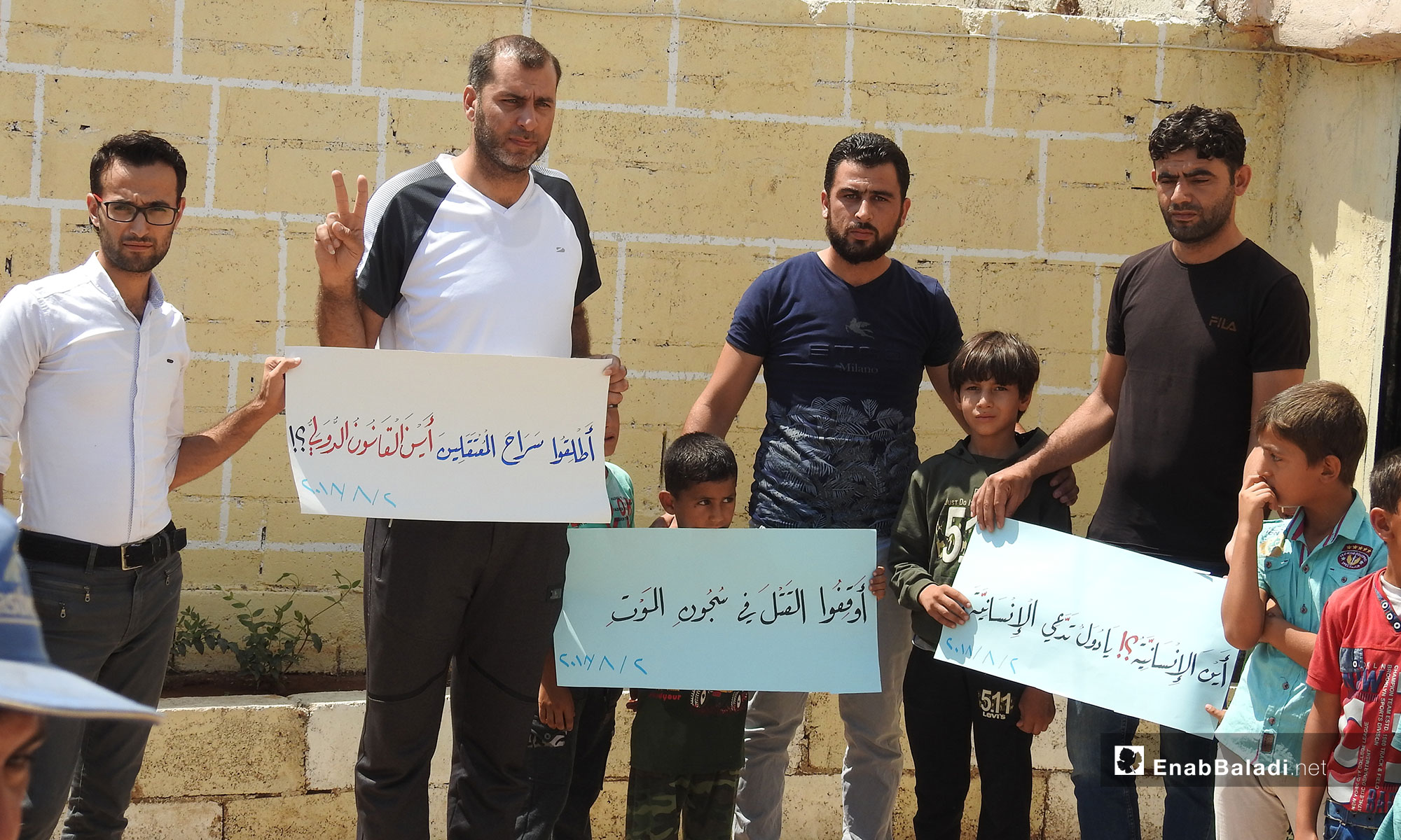 A Sit-in in the town of Dabiq protesting the violations of Syrian detainees' rights, northern rural Aleppo (Signs in Arabic from left to right say: Release the detainees, where is the international law, Stop the killing in death prisons, Where is humanity, you states claiming being humanitarian) – August 2, 2018 (Enab Baladi)