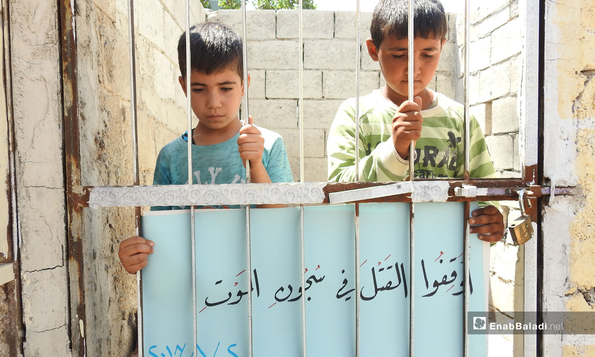 Two children from the town of Dabiq demand that violations against Syrian detainees be stopped, northern rural Aleppo (The sign says: Stop the killing in death prisons) – August 2, 2018 (Enab Baladi)