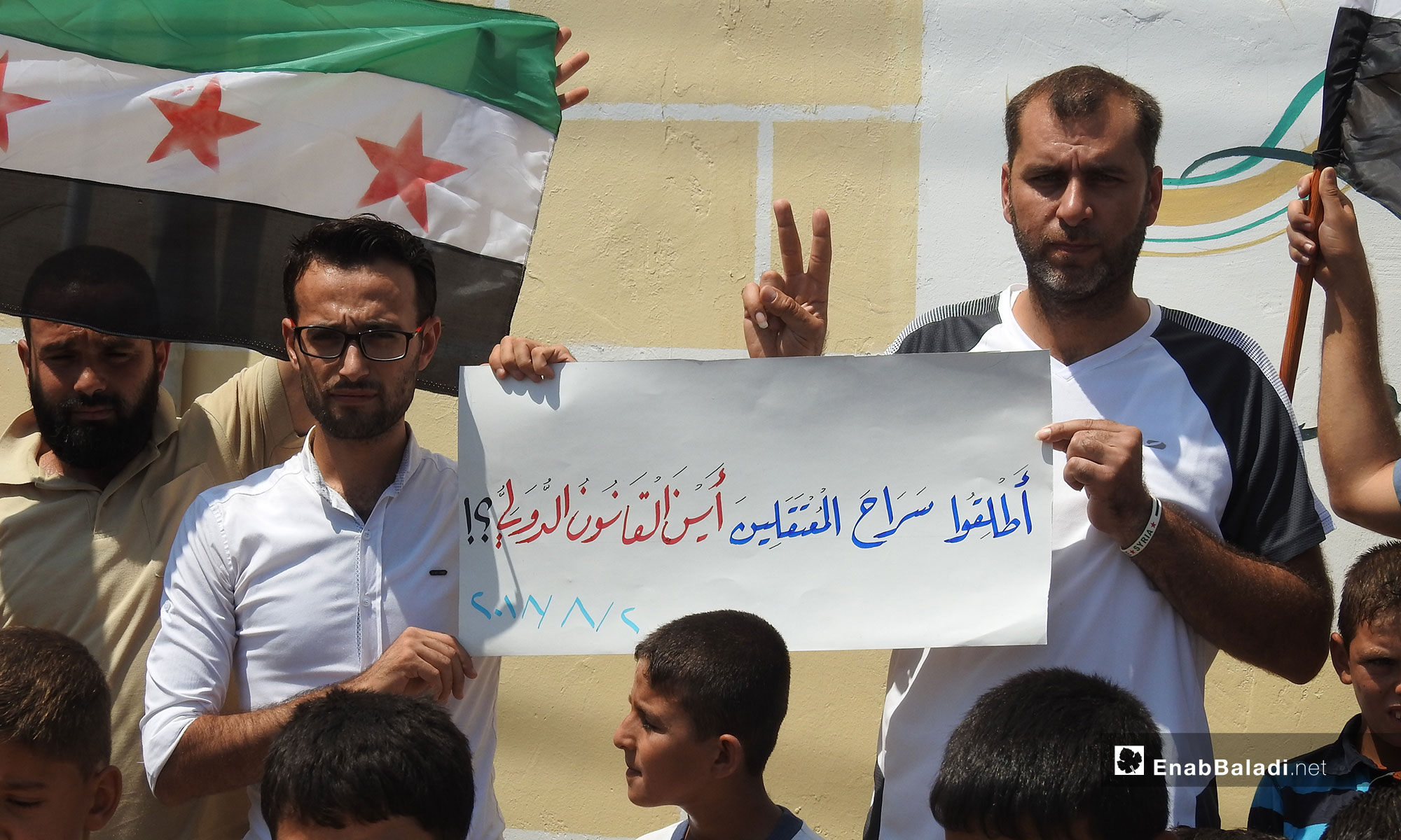 A Sit-in in the town of Dabiq protesting the violations of Syrian detainees' rights, northern rural Aleppo (the sign in Arabic says: Release the detainees, where is the international law) – August 2, 2018 (Enab Baladi)