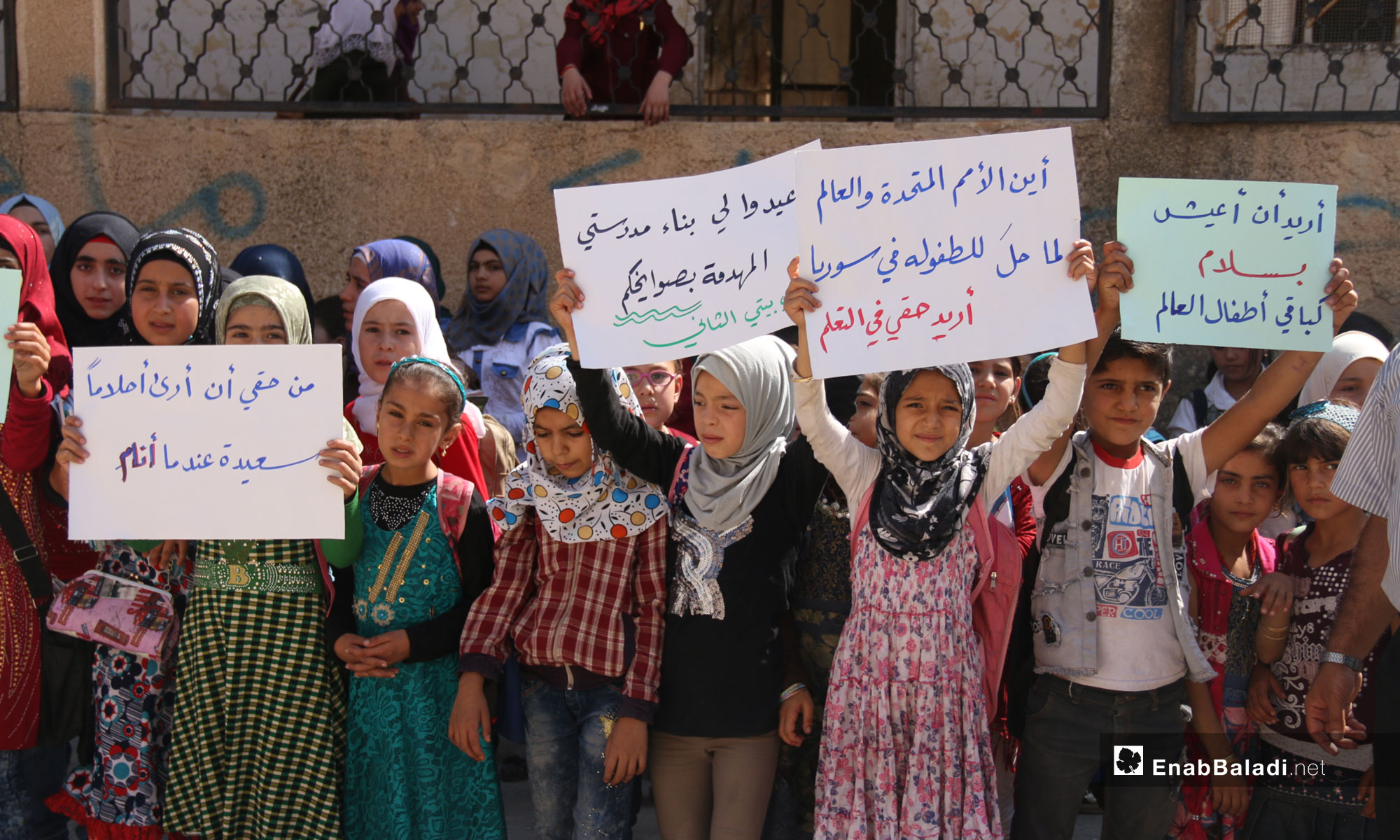 A protest organized by the educational staff of Kafr Oweid Town, rural Idlib, calling for the support of education in the liberated areas [Signs from left to right say: I have the right to see sweet dreams at sleep/ rebuild my school, destroyed by your missiles; my school is my second home/ Where are UN and the World in all that happened to childhood in Syria; my right to education/ I want to live in peace like the rest of the world's children] – September 19, 2018 (Enab Baladi)